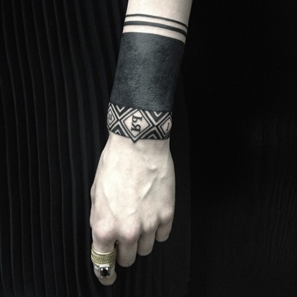 Wonderful blackwork wrist tattoo by Sasha Masiuk