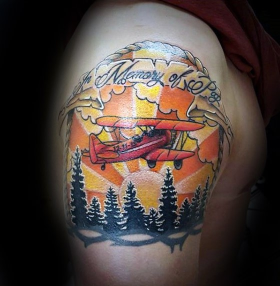Wonderful illustrative style shoulder tattoo of flying plane with forest and lettering