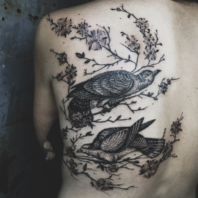 Wonderful looking black and white engraving style birds tattoo on back combined with blooming tree