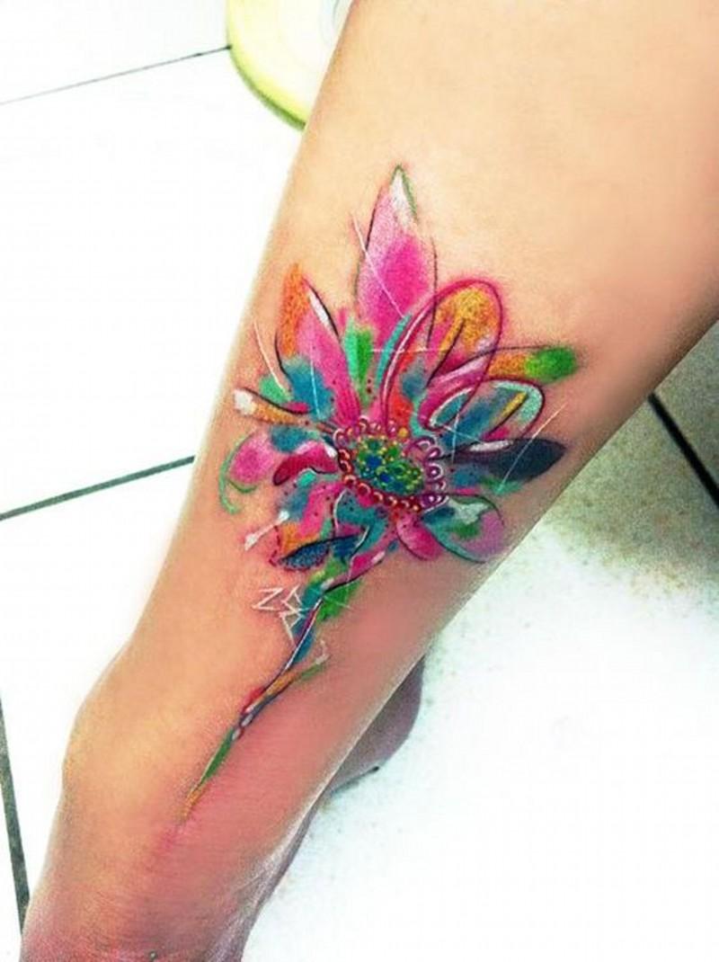 Wonderful watercolor like colored little flower tattoo on leg