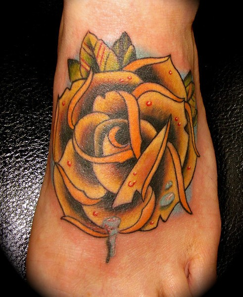 Tatuaggio colorato sul piede la rosa gialla