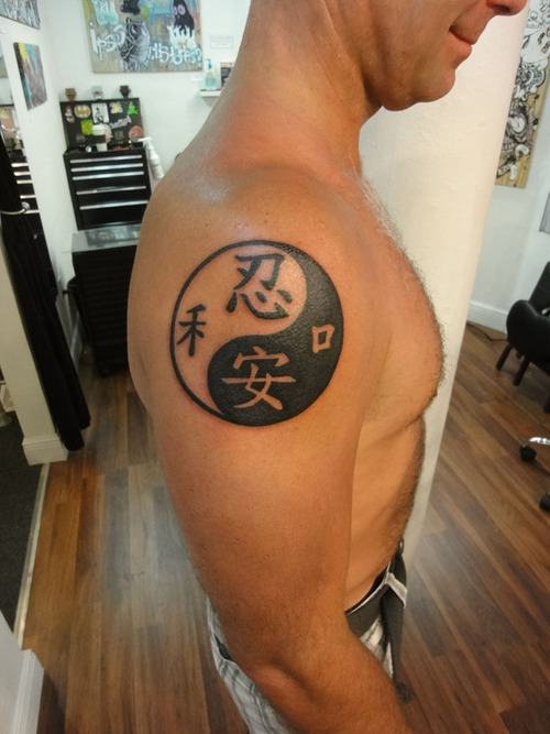 Tatuaggio grande sul deltoide il disegno nero in stile Yin-Yang